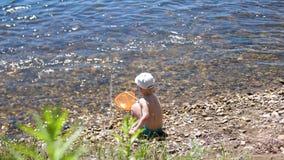 Рыболовная сеть мальчика на речном береге Красивейший ландшафт лета воссоздание обеда напольное Летние отпуска в деревне видеоматериал