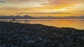 Рыболовная удочка против красивого захода солнца на зиме видеоматериал