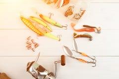 Рыболовная удочка с вьюрком, приманками ложки, снастями и wobblers в коробке для улавливать или удить захватническую рыбу на бело Стоковая Фотография