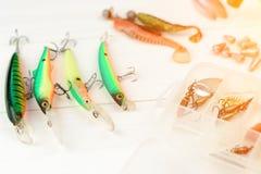Рыболовная удочка с вьюрком, приманками ложки, снастями и wobblers в коробке для улавливать или удить захватническую рыбу на бело Стоковые Изображения RF
