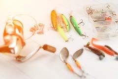 Рыболовная удочка с вьюрком, приманками ложки, снастями и wobblers в коробке для улавливать или удить захватническую рыбу на бело Стоковое Изображение