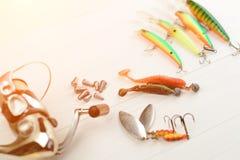 Рыболовная удочка с вьюрком, приманками ложки, снастями и wobblers в коробке для улавливать или удить захватническую рыбу на бело Стоковое Фото