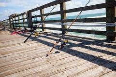 Рыболовные удочки на деревянных морских моле или пристани Стоковое Фото