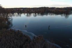 Рыболовы на первом льде на реке Тонкий лед реки с отражениями стоковое фото rf