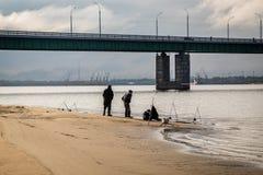Рыболовы на песочном речном береге около моста Стоковая Фотография
