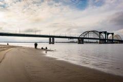 Рыболовы на песочном речном береге около моста Стоковые Изображения RF