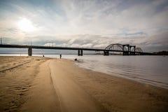 Рыболовы на песочном речном береге около моста Стоковая Фотография RF