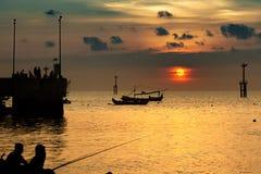 Рыболовы удя на пристани на заходе солнца Силуэты шлюпок в порте на заходе солнца стоковая фотография rf
