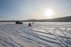 Рыболовы улавливают рыб на снежном озере, в свете вечера Стоковые Фото