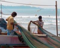 Рыболовы al  LoÑ стоят на шлюпке и распутывают, рыболовная сеть ряда, в пляже океана предпосылки стоковая фотография