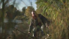 Рыболов бежит к штанге и хватает его, но избежания рыб Бородатый человек удит на речном береге видеоматериал