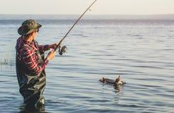 Рыболов в красной рубашке уловил судака в пресноводном пруде стоковая фотография