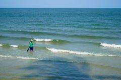 Рыболов в красочной рубашке и брюках ждать с сетью для удить на пляже с мягкими волной моря и тенью кокосовой пальмы Стоковое фото RF