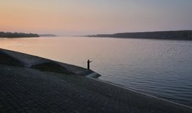 Рыболов в моментах захода солнца на стороне Дуная Стоковое Изображение RF