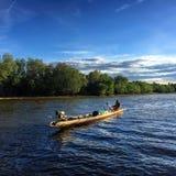 Рыболов гребля на реке стоковое фото