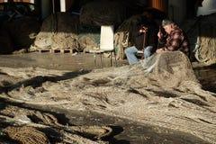 Рыболов и его сети стоковая фотография
