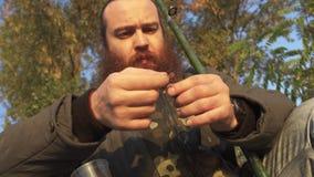 Рыболов кладет червя на крюк Портрет бородатого удя человека сток-видео