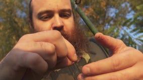 Рыболов кладет червя на крюк Портрет взрослого удя человека с бородой сток-видео