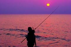 Рыболов морем на заходе солнца Стоковое фото RF