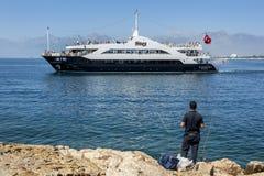 Рыболов наблюдает, как туристическое судно двигает через залив Антальи в Турции Стоковая Фотография RF