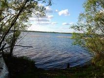 Рыболов на береге большого озера смотрит через бинокли Стоковые Фотографии RF