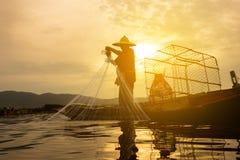Рыболов на деревянной шлюпке бросая сеть для задвижки рыба Стоковое Изображение RF