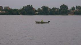 Рыболов на малой старой шлюпке в середине реки удит для приманки Отдых и хобби неизвестного человека акции видеоматериалы