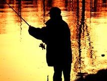 Рыболов на озере во время захода солнца Стоковая Фотография RF