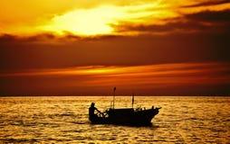 Рыболов на шлюпке над драматическим заходом солнца Стоковые Фотографии RF