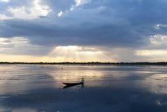 Рыболов на шлюпке с заходом солнца стоковая фотография rf