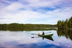 Рыболов плавает на зеленой шлюпке на озере Стоковые Изображения RF