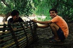 рыболов подготавливая их бамбуковые ловушки рыб для того чтобы установить его на Меконг стоковые фото