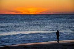 Рыболов прибоя наблюдая восход солнца стоковое изображение rf