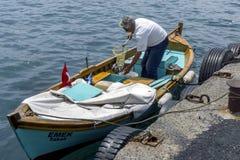 Рыболов разгржает его задвижку от шлюпки состыкованной на золотом рожке на Стамбуле в Турции стоковые фотографии rf