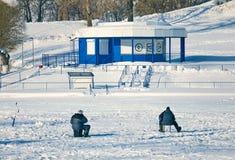 Рыболов 2 сидя в середине замороженного озера ждать рыб стоковое изображение rf