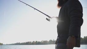 Рыболов с бородой удит на речном береге в солнечности Рыбная ловля человека с рыболовной удочкой на реке Река сток-видео