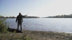 Рыболов с бородой удит на речном береге Рыбная ловля человека с рыболовной удочкой на реке Рыбная ловля реки медленно сток-видео