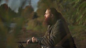 Рыболов с длинной рыбной ловлей бороды на речном береге Fisher штрихует его бороду Рыбная ловля реки сток-видео