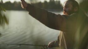 Рыболов с длинными рыбами задвижек бороды сидя на речном береге Fisher развевает его greetiings руки его друг Река видеоматериал