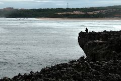 Рыболов с закручивать на пляж в утесах пляжа в Бали Стоковое Изображение