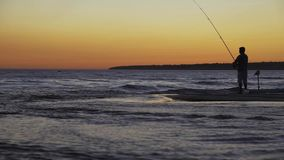 Рыболов с закручивая заходом солнца силуэта на море акции видеоматериалы