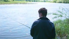 Рыболов с рыболовной удочкой на речном береге Красивейший ландшафт лета воссоздание обеда напольное хобби видеоматериал