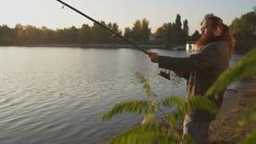 Рыболов удит с рыболовной удочкой Fisher поднимает и понижает закручивать акции видеоматериалы