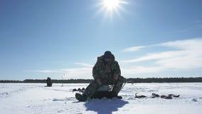 Рыболов улавливает рыбу, спорт зимы, хобби зимы видеоматериал