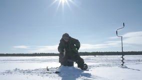 Рыболов улавливает рыбу, спорт зимы, хобби зимы сток-видео