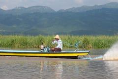 Рыболов управляя в деревянной шлюпке на озере inle в Мьянме стоковые изображения