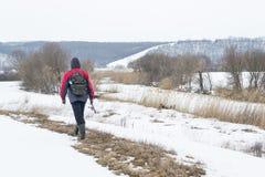 Рыболов человека в теплой куртке идет на рыбную ловлю зимы стоковые изображения rf