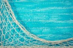 Рыболовная сеть на старой голубой доске стоковые изображения rf