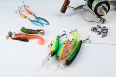 Рыболовная удочка с вьюрком, приманками ложки, снастями и wobblers в коробке для улавливать или удить захватническую рыбу на бело Стоковые Фото