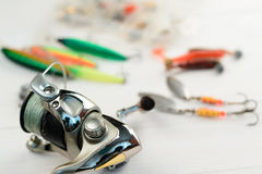Рыболовная удочка с вьюрком, приманками ложки, снастями и wobblers в коробке для улавливать или удить захватническую рыбу на бело Стоковое фото RF